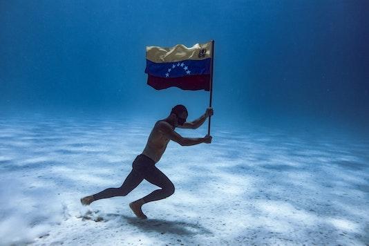 person holding venezuelan flag underwater